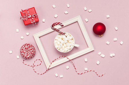 White mug with marshmallows Candy Cane gifts boxes red ball packaging lace photo frame on pink background top view Flat Lay. Winter traditional drink food Festive decor celebration Christmas New Year
