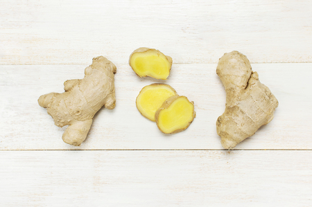 Whole and sliced fresh ginger roots on white wooden background top view copy space. Minimalistic style, seasoning, spice, ingredient for tea. Concept healthy food, medicine improving immunity