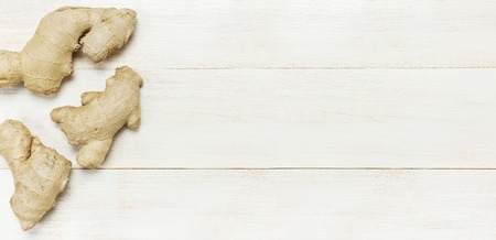 Fresh Ginger root on white wooden background top view with copy space. Minimalistic style, seasoning, spice, ingredient for tea. Concept healthy food, medicine improving immunity