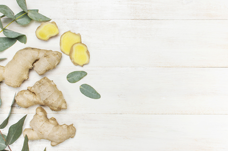 Whole and sliced fresh ginger roots, eucalyptus on white wooden background top view copy space. Minimalistic style, seasoning spice ingredient for tea Concept healthy food medicine improving immunity 写真素材