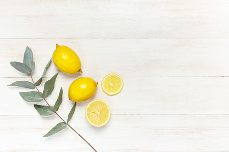 Whole and sliced fresh lemon, eucalyptus leaves on white wooden background. Flat lay, top view, copy space. Minimal fruit concept design. Yellow citrus lemons