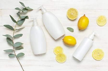 Whites Cosmetic bottle containers, fresh lemon eucalyptus on white wooden background top view flat lay copy space. Blank label for branding mock-up Natural beauty product concept Shower Gel Soap Cream Foto de archivo