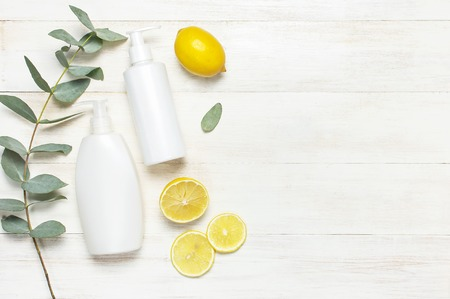 Whites Cosmetic bottle containers, fresh lemon eucalyptus on white wooden background top view flat lay copy space. Blank label for branding mock-up Natural beauty product concept Shower Gel Soap Cream Stock Photo
