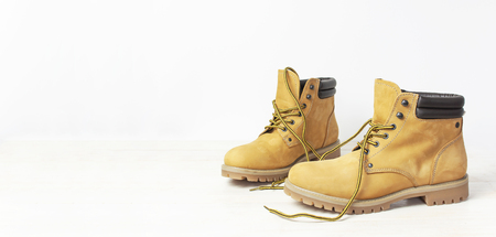 Yellow men's work boots from natural nubuck leather on wooden white background. Trendy casual shoes, youth style. Concept of advertising autumn winter shoes, sale, shop
