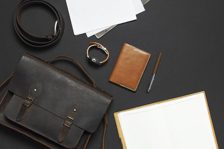 Fashionable concept. Brown leather men's bag, wristwatch, leather passport cover, pen, blank white sheets on black background top view flat lay with copy space Accessories businessman stylish clothes