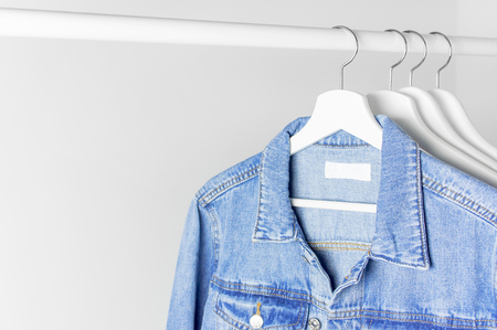 Blue denim jacket on white wooden coat hanger on a rod against light gray wall flat lay copy space. Denim, fashionable jacket, women's or men's trend clothing, fashion background. Store concept, sale