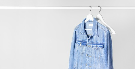 Blue denim jacket on white wooden coat hanger on a rod against light gray wall flat lay copy space. Denim, fashionable jacket, women's or men's trend clothing, fashion background. Store concept, sale Stockfoto