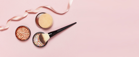 Ball pearl blush, face powder, makeup brush and pink ribbon on a pastel pink background top view Flat Lay with copy space. Various cosmetic products, Makeup Accessories