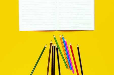 Color pencils and clean notebook in line on yellow background top view flat lay copy space. Wooden colored pencils for drawing, objects for creativity, school supplies close-up. Back to school concept