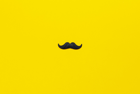 Black mustache, props for photo booths, carnival, parties on yellow background top view flat lay copy space. Fathers day, Creative party decoration concept. Mens health awareness month.