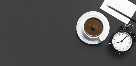 Flat lay cup of black coffee, black alarm clock, pencil, white cards on gray dark background top view copy space. Minimalistic food concept, morning breakfast time to work hot drink coffee background 版權商用圖片