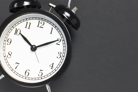 Black retro alarm clock on gray dark background top view Flat lay copy space. Minimalistic background, concept of time, deadline, time to work morning Banque d'images
