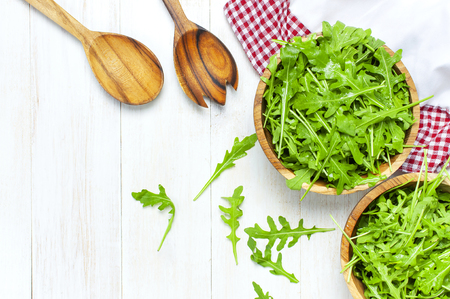 Fresh green arugula leaves on wooden bowl, rucola salad on white wooden rustic background top view with place for text. Rocket salad or arugula, healthy food, diet. Nutrition concept