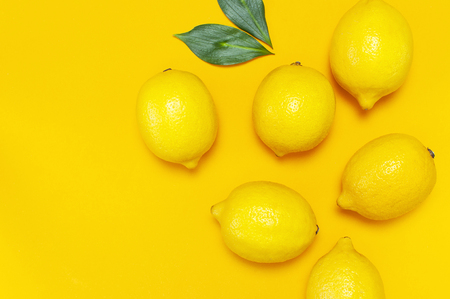 Ripe juicy lemons and green leaves on bright yellow background. Lemon fruit, citrus minimal concept, vitamin C. Creative summer food minimalistic background. Flat lay, top view, copy space Imagens