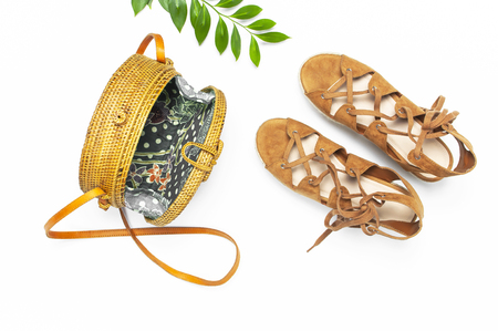 Fashionable handmade natural organic rattan bag, sandals, green twig on white background. Ladies bag Female fashion background. Flat lay, top view, copy space. Ecobags from Bali. Stylish rattan bag.