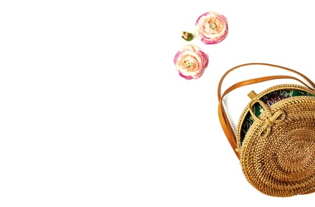 Fashionable handmade natural organic rattan bag and green fern leaves, pink flower isolated on white background. Ladies bag, Stylish rattan bag. Flat lay, top view, copy space. Ecobags from Bali