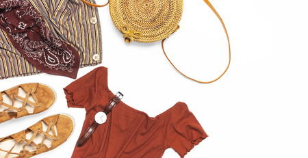 Stylish trendy feminine summer clothing skirt jacket suede sandals round rattan bag shawl wrist watch on white background. Female fashion background beauty or fashion blog concept Flat lay top view.