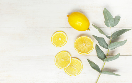 Whole and sliced fresh lemon, eucalyptus leaves on white wooden background. Flat lay, top view, copy space. Minimal fruit concept design. Yellow citrus, lemons.