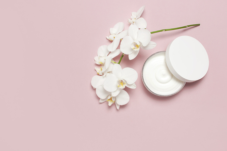 Beauty Spa concept. Opened plastic container with cream and White Phalaenopsis orchid flowers on pink background Flat lay top view Herbal dermatology cosmetic hygienic cream, organic cosmetic Natural Imagens