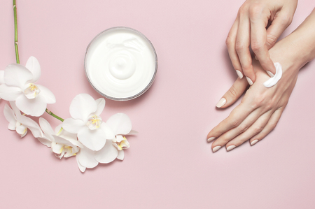 Young woman moisturizes her hand with cosmetic cream lotion opened container with cream body milk White Phalaenopsis orchid flowers on pink background Flat lay top view minimalism style Beauty concept. 免版税图像
