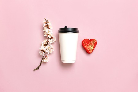Coffee or tea paper cup, heart-shaped macaroon cakes, spring branches of white flowers on pink background top view flat lay. Take away coffee cup, mockup. Coffee love concept, layout for design.