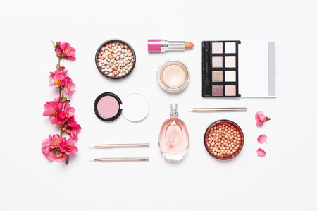 Different makeup cosmetic. Ball blush rouge face powder lipstick concealer bottle of perfume eyeshadow makeup brush spring pink flowers on light background top view flat lay. Beauty fashion background.
