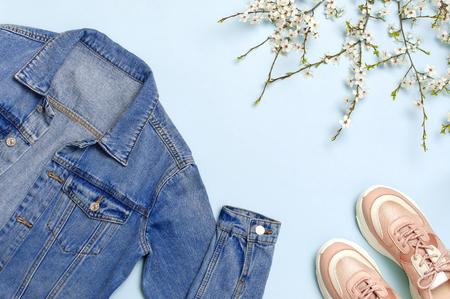 Blaue Jeansjacke, trendige rosa Turnschuhe, Frühlingsblumen auf blauem Hintergrund Draufsicht flach Kopienraum. Denim, modische Jacke, Damen- oder Herren-Trendkleidung, Frühlingsmode-Beauty-Hintergrund