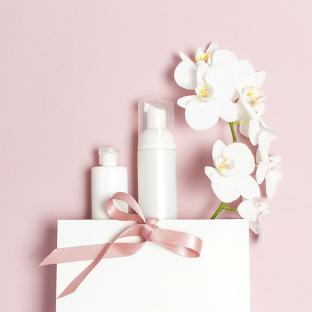 Marken-Mock-up für Kosmetik SPA. Flache Ansicht von oben Weiße kosmetische Flaschenbehälter Geschenktüte Weiße Phalaenopsis Orchideenblüten auf rosa Hintergrund. Natürliches organisches Schönheitsproduktkonzept.