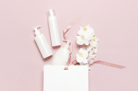 Cosmetics SPA branding mock-up. Flat lay top view White cosmetic bottle containers gift bag White Phalaenopsis orchid flowers on pink background. Natural organic beauty product concept.
