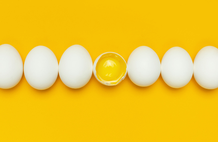 White chicken eggs and one broken egg with yolk on yellow background top view flat lay copy space. Creative food minimalistic background, Easter. Natural healthy food and organic farming concept