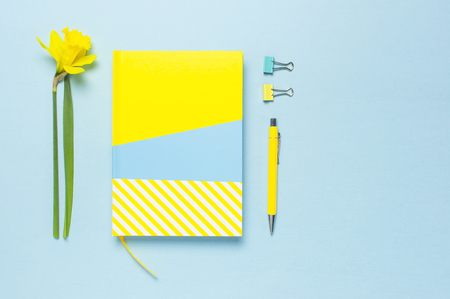 Yellow-blue notebook, pen, clips, spring flowers daffodils narcissus on blue background. Female desktop, Office desk, spring concept. Flat lay, top view, copy space. Template for feminine blog. Imagens