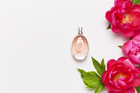 Perfume bottle and pink flowers peonies on light gray background top view Flat lay copy space. Perfumery, cosmetics, female accessories, fragrance collection. Delicate Pink Perfume Bottle.