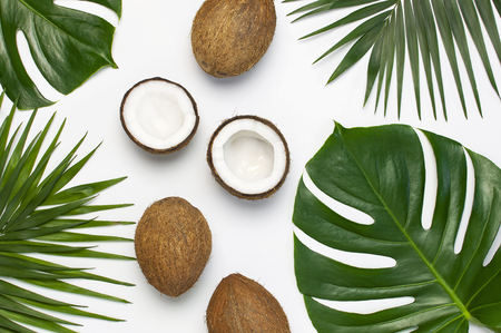 Tropical leaves and fresh coconut on light gray background. Flat lay, top view, copy space. Summer background, nature. Healthy cooking. Creative healthy food concept, half of coconut. 스톡 콘텐츠