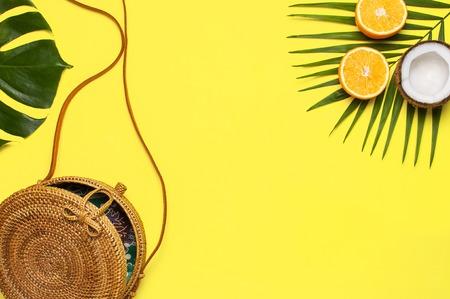 Mise à plat de la mode estivale. Sac rond en rotin tendance, feuilles de palmiers tropicaux, feuille de monstre, noix de coco, orange sur fond jaune. Espace de copie vue de dessus. Sac en bambou tendance. Concept de vacances de fond créatif.