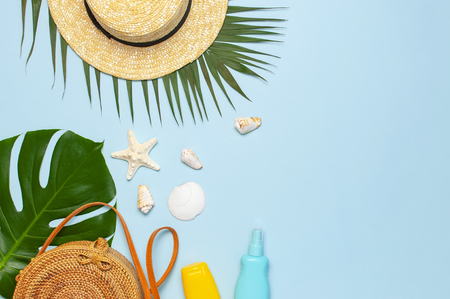 Summer composition flat lay. Round trendy rattan bag straw hat tropical palm leaves coconut sunscreen seashells on blue background. Top view copy space. Creative fashion vacation backdrop. Archivio Fotografico