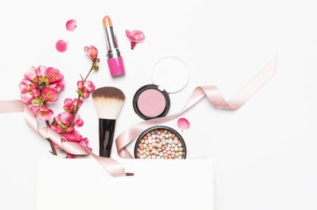 Different makeup cosmetic. Ball blush rouge lipstick concealer bottle of perfume makeup brush spring pink flowers in white gift package on light background top view flat lay. Beauty fashion background. Reklamní fotografie