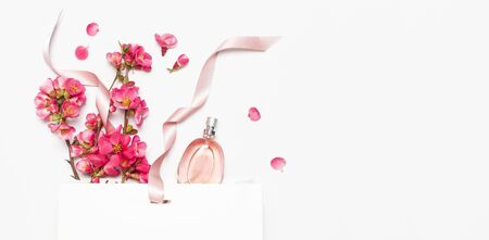 Bottle of womens perfume with pink spring flowers white gift package on light background top view flat lay copy space. Perfumery cosmetics female accessories fragrance collection. Perfume Bottle.