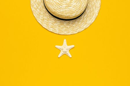 Women s summer straw hat, starfish on yellow background top view flat lay copy space. Summer travel vacation concept, single item. Female accessory, summer background. Banco de Imagens