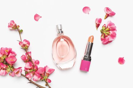 Bottle of womens perfume and lipstick with pink spring flowers on light gray background top view flat lay copy space. Perfumery, cosmetics, female accessories, fragrance collection. Perfume Bottle. Reklamní fotografie