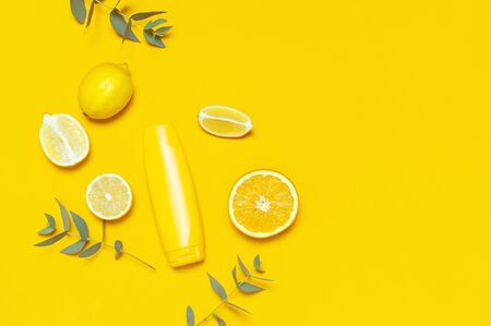 Yellow Cosmetic bottle containers, citrus lemon, orange, eucalyptus on yellow background top view flat lay copy space. Blank label for branding mock-up Natural beauty product sunscreen Summer concept.