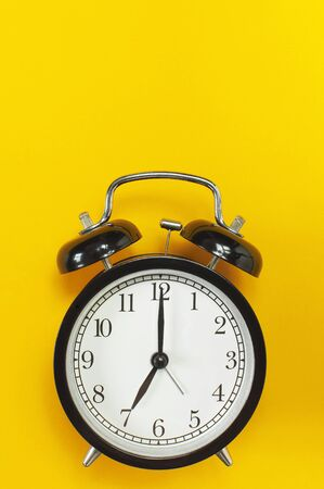 Black retro alarm clock on yellow background top view Flat lay copy space. Minimalistic background, concept of time, deadline, time to work, morning.