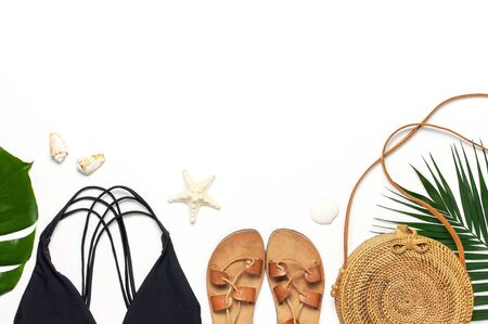 Woman's beach accessories flat lay. Round trendy rattan bag straw hat black swimsuit leather sandals tropical palm leaves seashells on white background. Top view copy space. Summer backdrop.