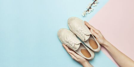 Female hands hold beige fashionable espadrilles with spring flowering branch on pastel blue pink background. Creative concept of spring shoes, fashion blog or magazine concept Flat lay top view. 스톡 콘텐츠