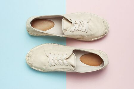 Beige fashionable womens espadrilles on color pastel blue pink background. Creative concept of spring shoes, fashion blog or magazine concept Flat lay top view copy space.