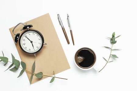 Flat lay cup of black coffee, black alarm clock, notebook, diary, eucalyptus on white background top view copy space. Minimalistic food concept, Feminine desk workspace, time to work coffee background.