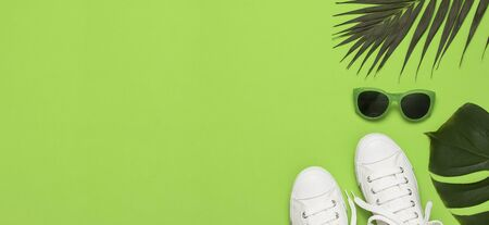 White female fashion sneakers, trendy sunglasses, tropical leaves on green background. Flat lay top view copy space. Womens shoes, accessories. Stylish white sneakers. Creative summer concept.