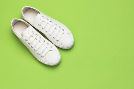 White female fashion sneakers on green background. Flat lay top view copy space. Womens shoes. Stylish white sneakers. Fashion blog or magazine concept. Minimalistic shoe background, sport shoes.