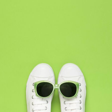 White female fashion sneakers and trendy sunglasses on green background. Flat lay top view copy space. Womens shoes, accessories. Stylish white sneakers. Creative concept Fashion blog or magazine.