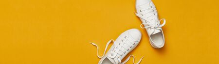 White female fashion sneakers on yellow orange background. Flat lay top view copy space. Womens shoes. Stylish white sneakers. Fashion blog or magazine concept. Minimalistic shoe background, sport.