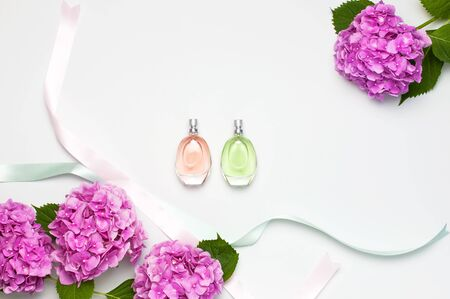Perfume bottles, pink hydrangea flowers, holiday ribbons on light background top view Flat lay copy space. Perfumery, cosmetics, female accessories, fragrance collection. Delicate Perfume Bottle.